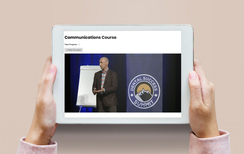 Hands holding a tablet with a communications training course on screen
