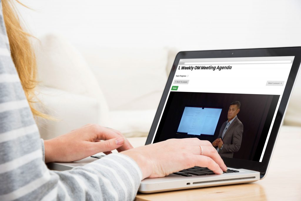 A figure in front of a laptop with a weekly meeting agenda on screen